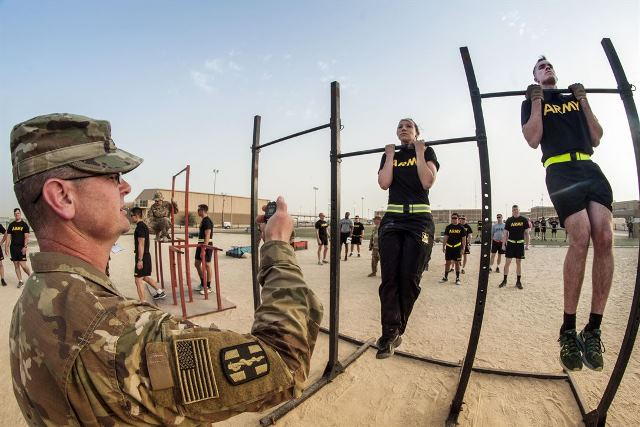 Soldiers participate in the flexed arm-hang during qualifications for the German Armed Forces Badge for Military Proficiency at Camp Arifjan, Kuwait, April 28, 2017