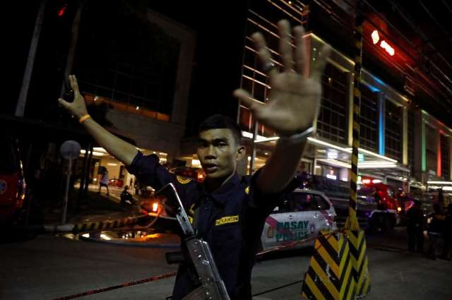 A security guard stops photographers from entering the vicinity of Resorts World Manila Pic Reuters