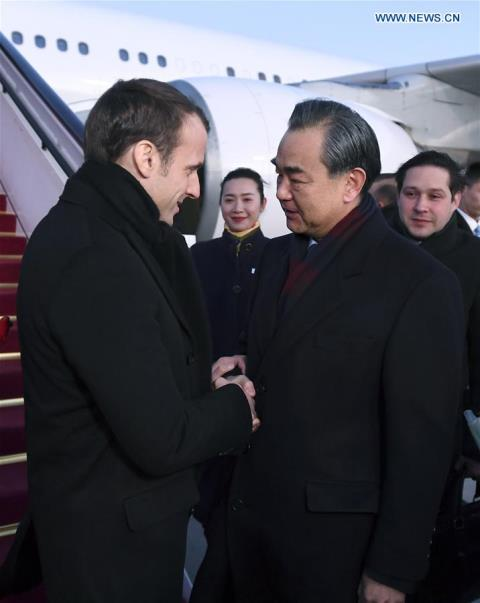 French President Emmanuel Macron is welcomed by Chinese Foreign Minister Wang Yi upon his arrival in Beijing