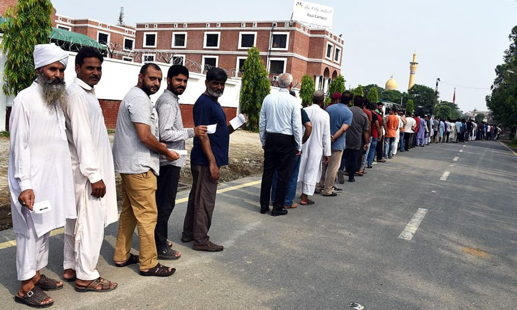 Voters stand in queue outside polling station in Johar Town, Lahore