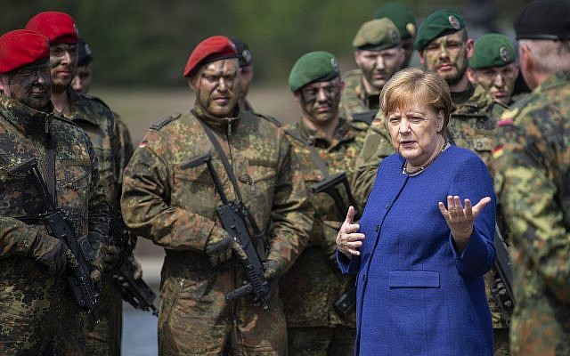 German Chancellor Angela Merkel, right, talks with NAO's VJTF unit Pic AP